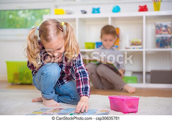 Cute little girl play game, boy read book