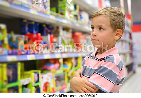 Boy looks at shelves with toys in shop - csp3064012
