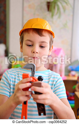 Boy in plastic helmet with toy tools - csp3064252