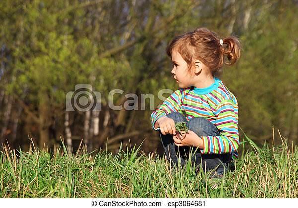 little girl with grass in hands sits on fringe of forest - csp3064681