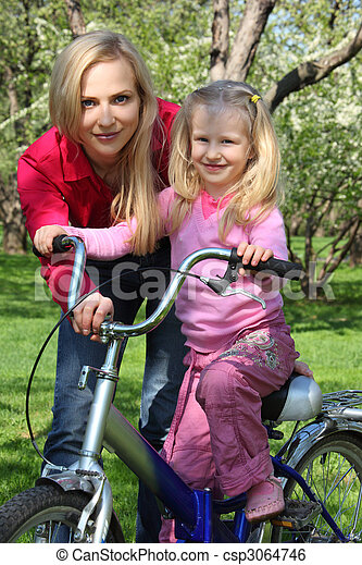 Mother with  daughter on bicycle in spring garden - csp3064746