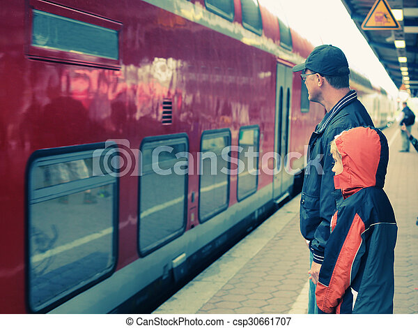 Father and 7 years old boy standing on a railway station and waiting for the train