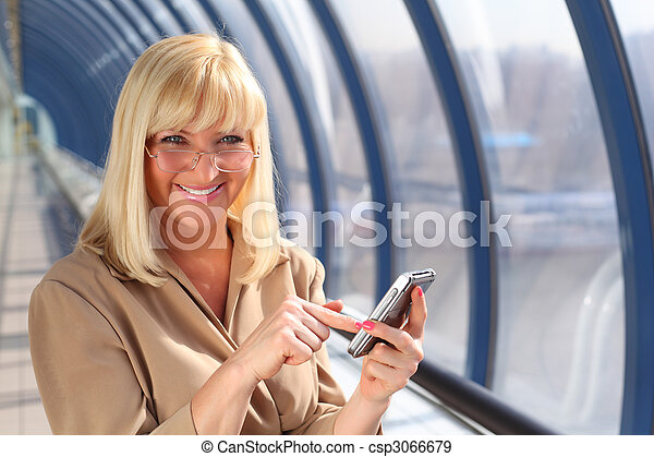 Smiling middleaged woman in glasses with on pda - csp3066679