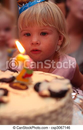 little girl blowing on birthday cake - csp3067146