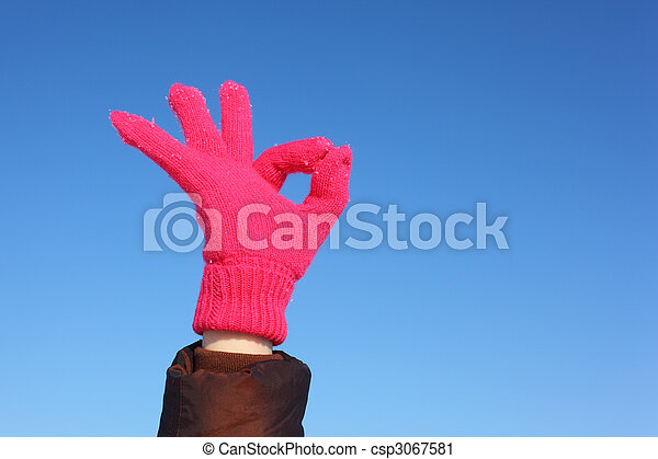 Hands in red glove against  blue sky shows gesture ok - csp3067581