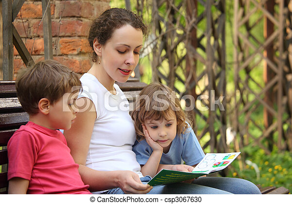 Mother reads book for children sits on bench - csp3067630