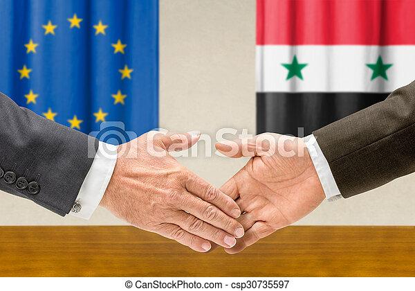 Representatives of the EU and Syria shake hands