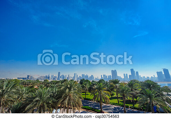 Palm trees and distant view of the city - csp30754563