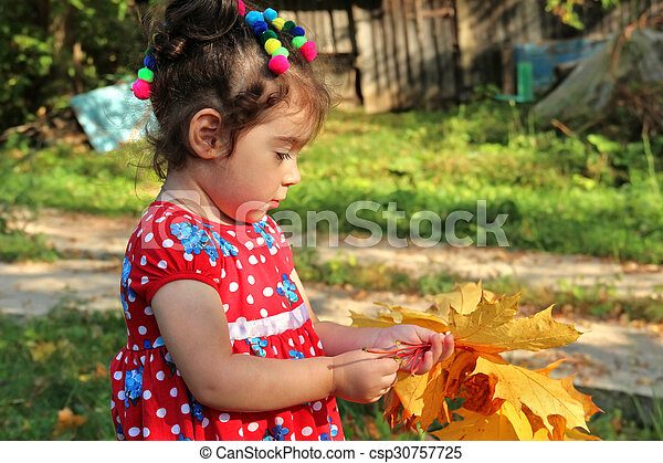 Little girl stands with bouquet of maple leaves in her hands