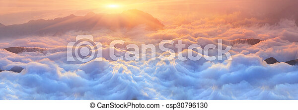 Bright saturated colors dawn above the sea of fog over the tops of the Carpathian is fabulously beautiful panoramic view, illuminated by the golden rays of the rising sun early in the morning
