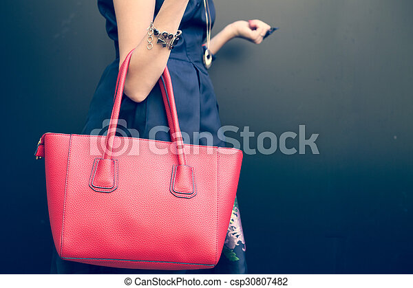 Fashionable beautiful big red handbag on the arm of the girl in a fashionable black dress, posing near the wall on a warm summer night. Warm color