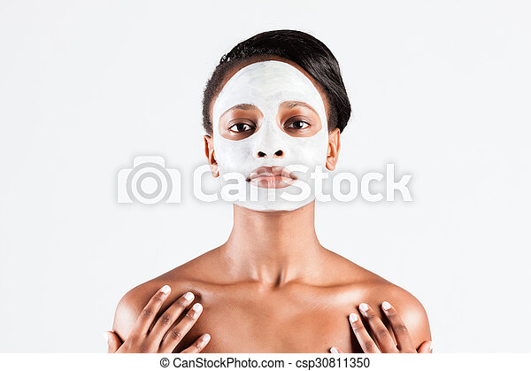 Beautiful African woman in Studio with facial mask - csp30811350