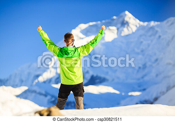 Man hiker or climber achievement in winter mountains