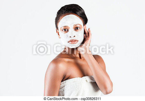 Beautiful African woman in Studio with facial mask - csp30826311
