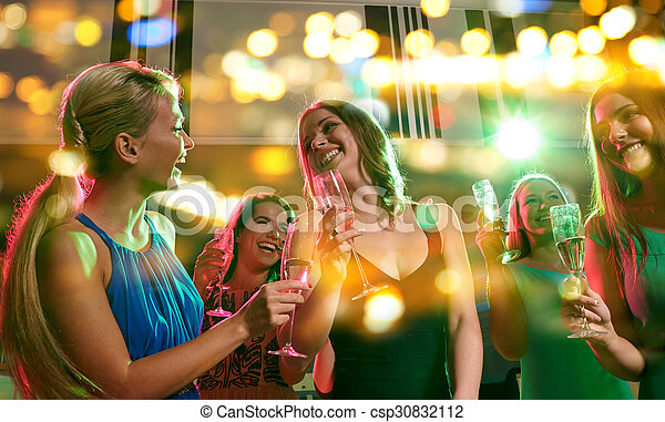 young women with glasses of champagne in club
