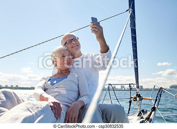 senior couple taking selfie by smartphone on yacht