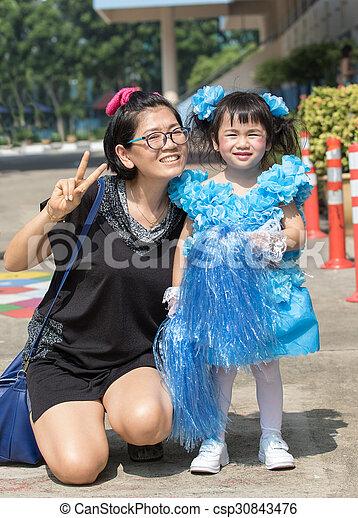 mother and young kid daughter wearing cheer leader dressing in kindergarten school sport day