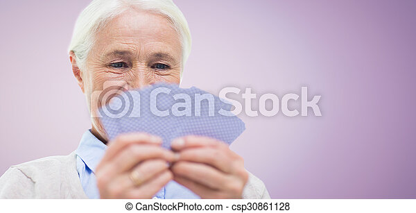 close up of happy senior woman playing cards