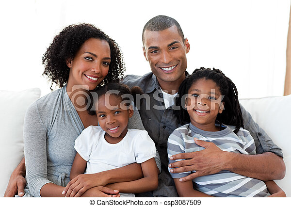 Loving family sitting on the sofa together - csp3087509
