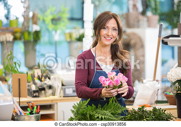 Happy Florist Making Bouquet Of Pink Roses In Shop