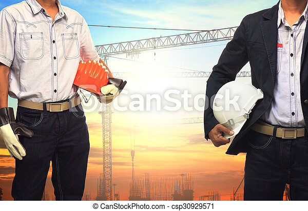 two engineer man working with white safety helmet against crane and building construction site use for civil engineering and construction industrial business