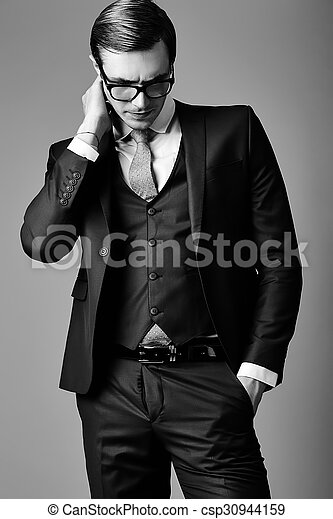 Young elegant handsome businessman male model in a suit and fashionable glasses, posing in studio