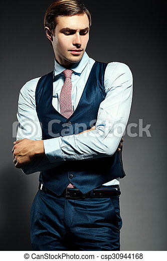 Young elegant handsome businessman male model in a suit posing in studio