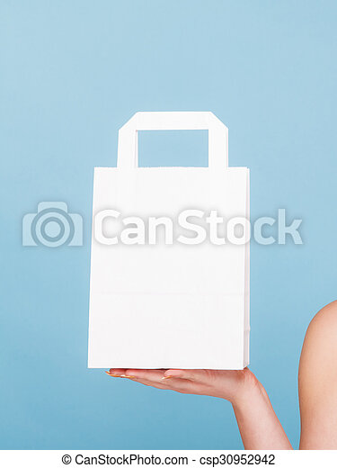 Female client customer woman presenting white paper shopping bag with copy space for text,. Retail sale and advertisement. Studio shot on blue.