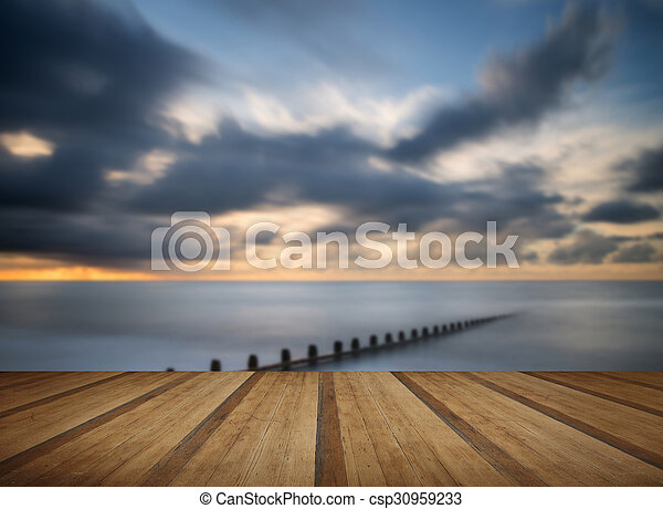 Beautiful long exposure vibrant concept image of ocean at sunset with wooden planks floor