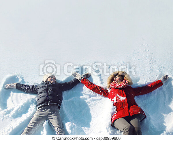 Happy mother and son playing and having fun together lying in the snow on a sunny winter day