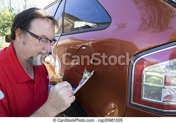 Insuance Adjuster Figuring Damages To Vehicle