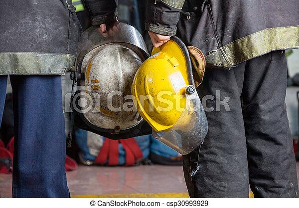 Firemen Holding Helmets At Fire Station