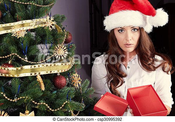 Unhappy young woman holding gift box