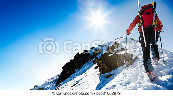 Ski mountaineer walking up along a steep snowy ridge with the sk