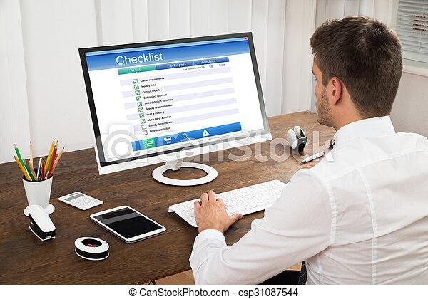 Businessman Filling Checklist Form On Computer