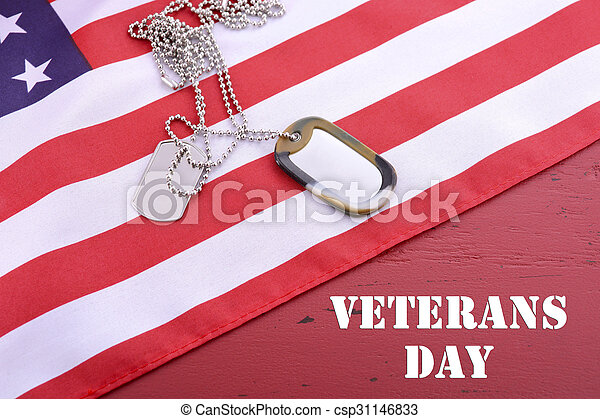Veterans Day USA flag with dog tags on rustic red wood background with sample text.