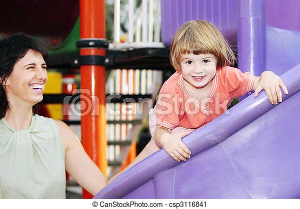 Child laughing in amusement park under supervision - csp3116841