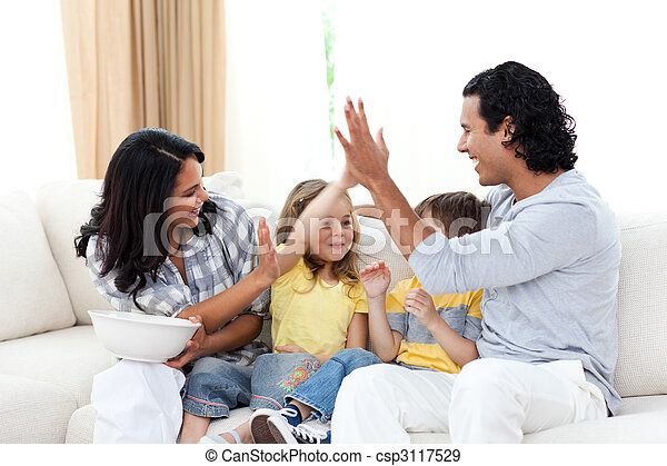Happy siblings watching TV with their parents - csp3117529