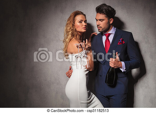side view of a hot couple holding a bottle of champagne