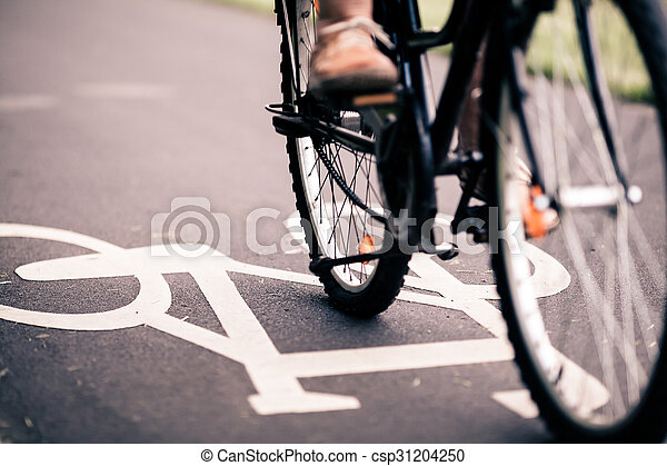 City bicycle riding on bike path, alternative ecological transportation. Commute on bicycle in urban environment, asphalt gray bike lane with bicycle markings