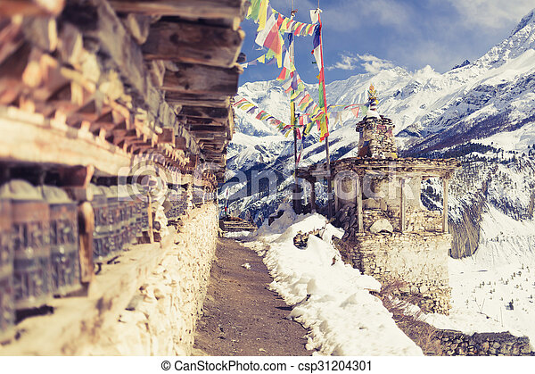Prayer wheels in high Himalaya Mountains, Nepal village. Focus on the stupa and prayers flags. Annapurna Two range region in Nepal, located at Annapurna Circuit Trekking Hiking Trail