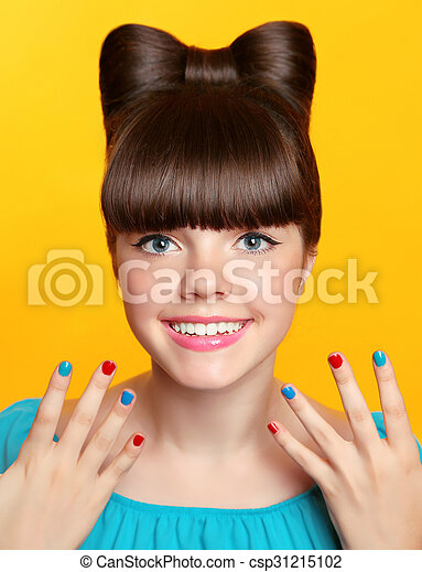 Smile. Beautiful happy smiling young teen girl with bow hairstyle and colourful manicured polish nails isolated on studio yellow background.