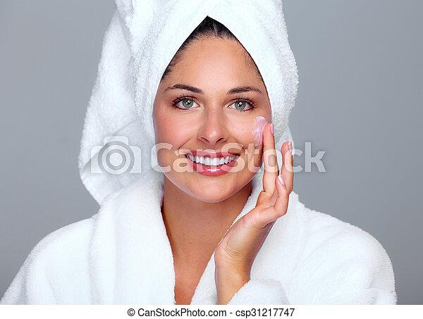 Beautiful woman face with moisturising cream.