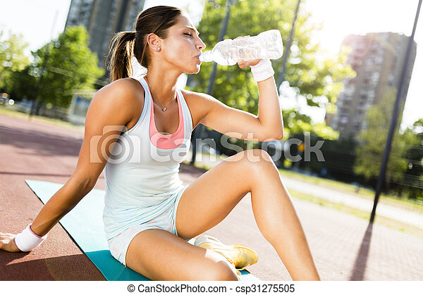 Young beautiful woman drinking water after exercise in a city training court