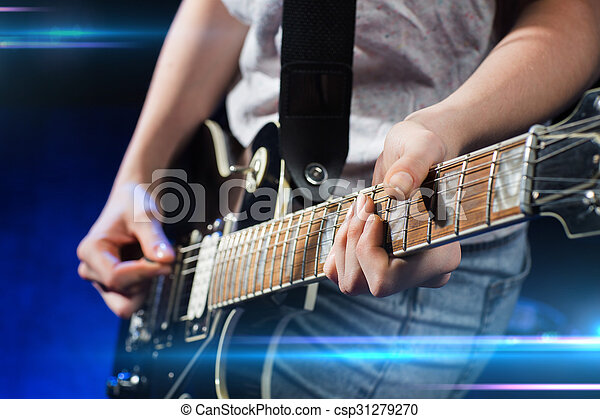 musician playing electric guitar with mediator