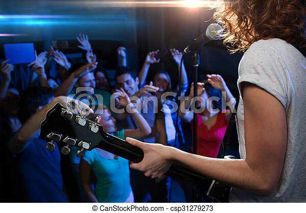female singer playing guitar over happy fans crowd