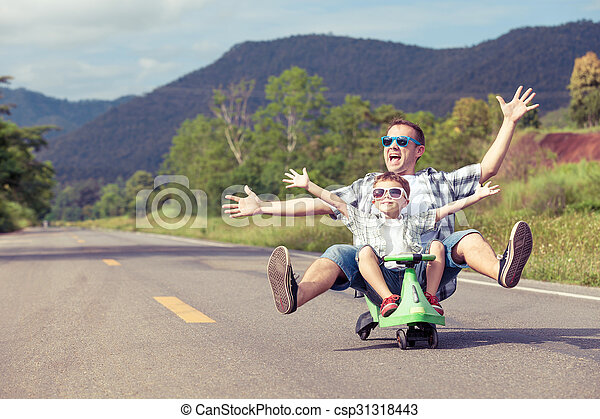 Father and son playing on the road.