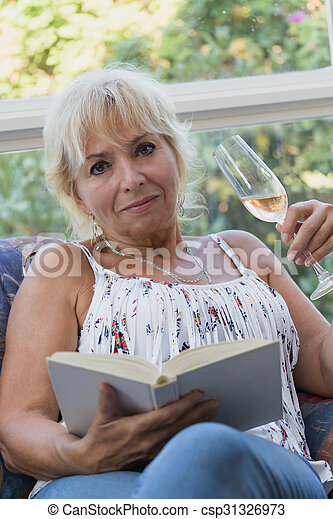 Senior mature blond woman with book and glass of champagne