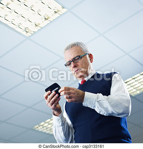 mature businessman reading e-mails on cellphone - csp3133161
