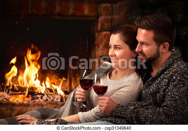 Couple relaxing with glass of wine at fireplace